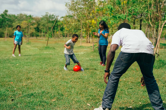 African American family with son and daughter plays a soccer together on the green field for relaxation - Family Bonding Recreation Sports Football Concept