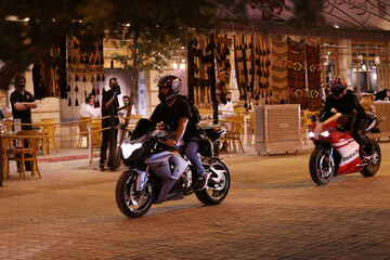 Saudi youth ride their motorbikes on Tahlia Street as nightlife kicks off, after the government loosened lockdown restrictions following the outbreak of the coronavirus disease (COVID-19), in Riyadh