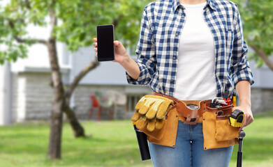 repair, construction and building concept - woman or builder with smartphone and working tools on...