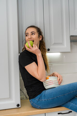 beautiful young woman eating fresh fruits on breakfast an early morning . in kitchen, diet