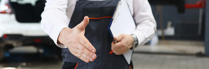Close-up of professional car mechanic offer to shake hands with customer. Male worker holding checklist paper. Automobile service station and restoration workshop concept