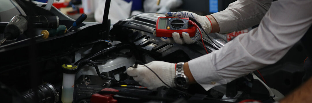 Close-up view of open trunk and male mechanic using multimeter or voltmeter checking a car battery level. Professional restoration workshop and repair concept