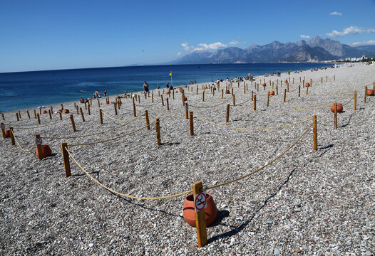Area marked by cordons of ropes and wooden stakes to enforce social distancing measures is seen on Konyaalti beach in Antalya