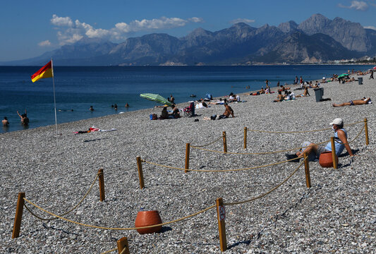 A man sits in an area marked by cordons of ropes and wooden stakes to enforce social distancing measures on the Konyaalti beach in Antalya