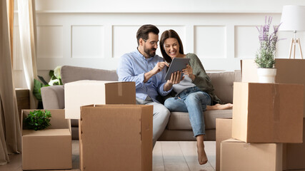 Excited young couple having fun with tablet on moving day, looking at mobile device screen, resting...