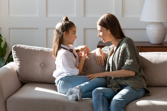 Caring mother and little daughter chatting, sitting on cozy couch in living room, pretty girl sharing secrets with loving mum, having pleasant conversation, good trusted family relationship