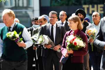 Britain's Secretary of State for Business, Energy and Industrial Strategy, Alok Sharma, holds flowers to place them near to the scene of reported multiple stabbings, as he is surrounded by faith leaders, in Reading