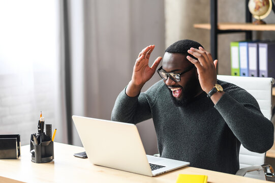 Overjoyed African man raised hands up, a guy in glasses excited and happy with a good news or deal, he looks at laptop screen with triumph