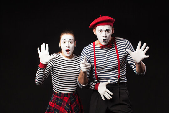 a man and a woman with white makeup on their faces like mimes  with funny emotions isolated on black background