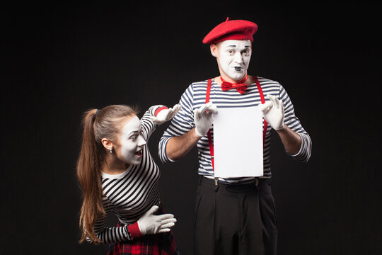 Two mimes man and woman  present white paper on isolated black background