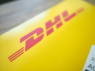 Red DHL sign over yellow envelope carton