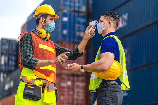 Professional of cargo foreman in helmets standing and using infrared thermometer for checking body temperature staff fever before work in quarantine for coronavirus wearing protective mask.covid19