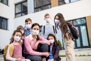 Group of children, teacher with face masks outdoors at school after covid-19 lockdown.