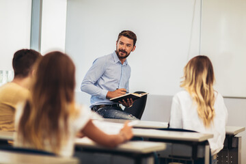 Smiling teacher standing in front of students and showing something on white board in classroom