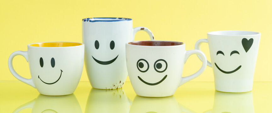 Four cups with funny faces on a color background. The concept of a friendly company, a big family, meeting friends for a cup of tea or coffee. Smiles on white coffee mug.