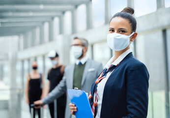 Portrait of flight attendant standing on airport, wearing face masks.