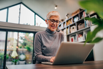 Portrait of a beautiful modern senior woman using laptop, low angle image. Fotobehang