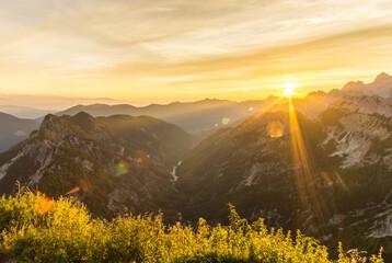 Wall Mural - Amazing sunrise in the mountains. Backlight Sunlight with beautiful lens flares and sunbeams. Julian Alps, Triglav National Park, Slovenia, Mountain Slemenova, Sleme.
