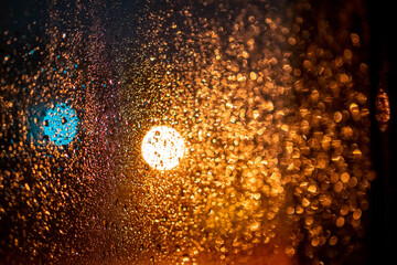 Raindrops on a window with abstract blurred colored lights