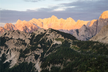 Wall Mural - Amazing sunrise in the mountains. Purpel orange Mountains of Julian Alps, Triglav National Park, Slovenia. View from Mountain Slemenova, Sleme to Mount Skrlatica.