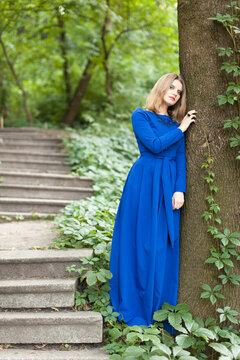 Beautiful blonde woman with make up in blue dress in the forest