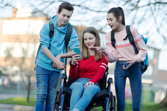 Teenage Friends With Girl In Wheelchair Looking At Mobile Phone As They Leave High School