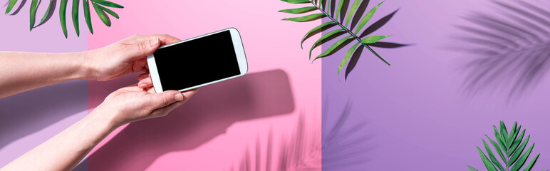 Smartphone with tropical palm leaves and shadow - flat lay