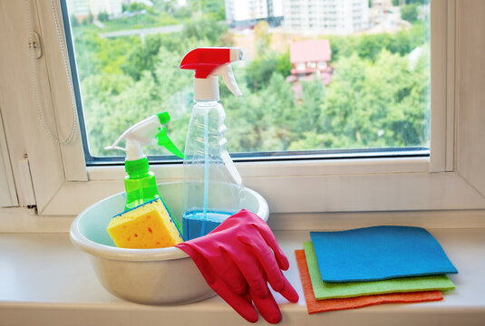 Set of window cleaning products - basin, spray bottles, rubber gloves, washcloth, multi-colored rags