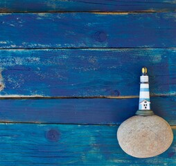 Flat lay image of boat and light house on rustic wood background. Some copy space