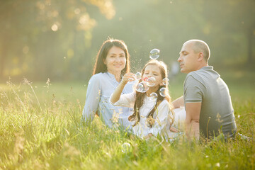 happy family with child girl blow soap bubbles together in park