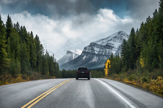 Rear of car driving on highway in the forest with mountain on gloomy