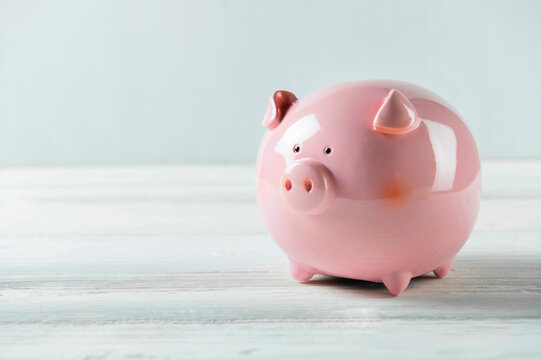 Pink Piggy bank on white wood floor. Financial and money savings concept. Copy space