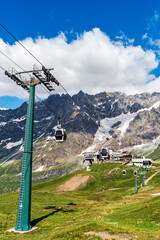 Cable cars near Cervino Mountain - Italy. Meadow, nature and a beautiful cloudy sky.