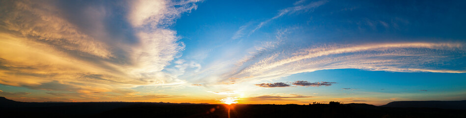 Wide panorama of sunset sky with clouds and sunlight over mountains , Panorama shooting