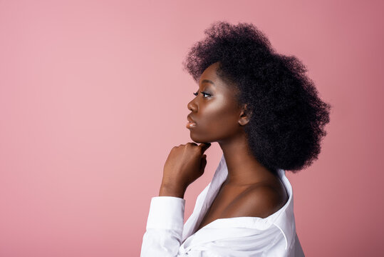 Elegant beautiful African American woman wearing classic white shirt,  posing in studio, on pink background. Close up profile portrait. Copy, empty space for text