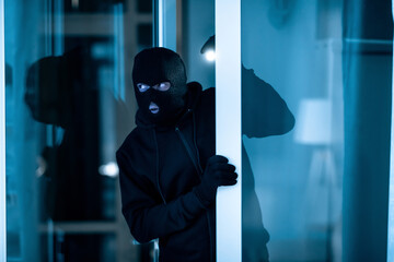 Thief breaking into apartment or office to steal something - fototapety na wymiar