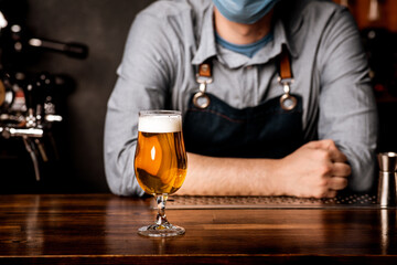 Bartender in protective mask leans on bar counter on which stands glass of light beer with foam