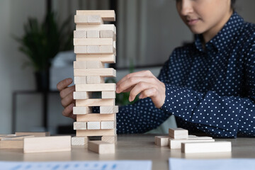 Indian businesswoman sitting at workplace desk build tower of wooden blocks play game, apply skills...