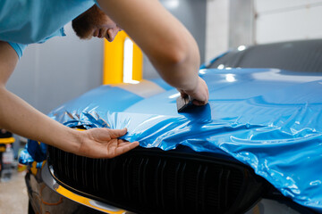 Car wrapper puts protective foil or film on hood
