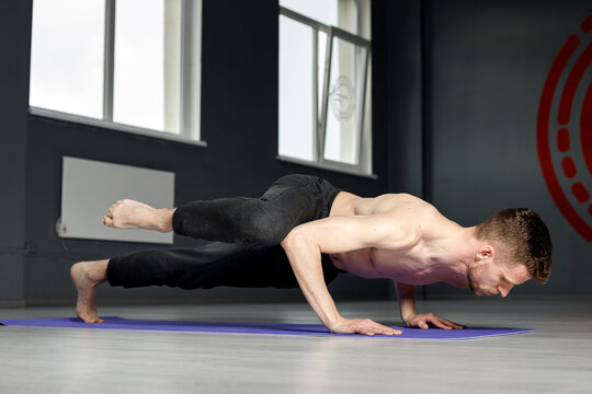 Young man is doing push-ups with knee tap.