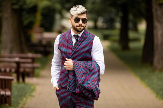 young business man in sunglasses and wearing on violet luxery three-piece suit looks to side while walking on street