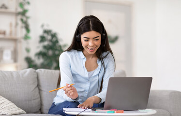 Online Education. Young Asian Girl In Headset Studying With Laptop At Home
