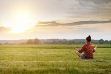 Woman relaxes on the grass in a field during a sunny sunset.