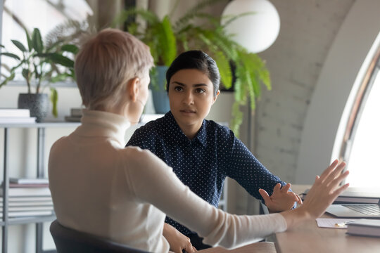 Indian and caucasian businesswomen negotiating sit at desk in office. Lawyer consulting client during formal meeting. Job interview and hiring process. Diverse colleagues discussing project concept
