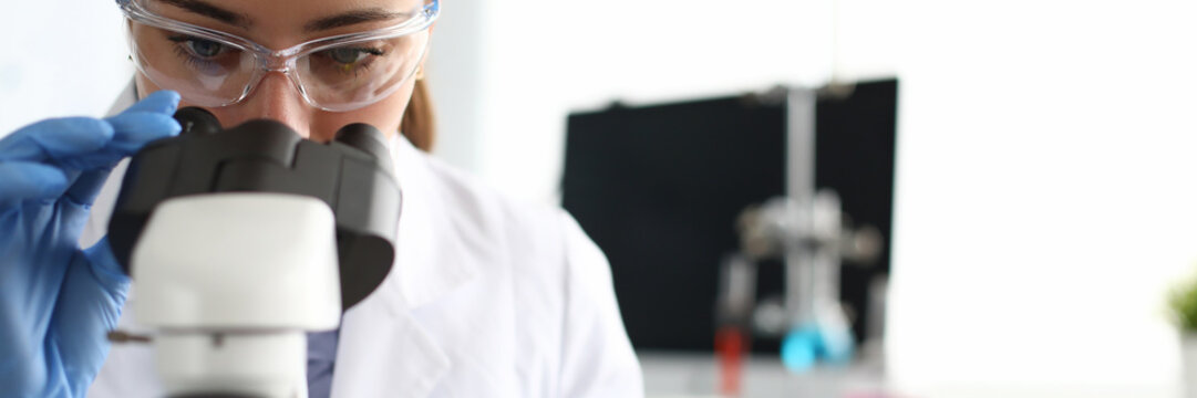 Close-up of scientist using microscope and test tubes. Laboratory assistant making analysing sample of medicines in research lab. Chemical experiments concept
