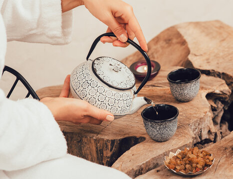 Woman pours wellness tea in spa after massage. Relaxation tea