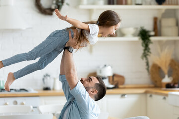 Close up preschool daughter flying with hands outstretched in caring father arms in modern kitchen....