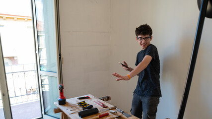 A work tools on a table: screwdrivers, hammers, pliers, utility knife and protective glasses can be seen. The boy jokes by stretching his hand towards the tools and in the other he holds a smartphone. Wall mural