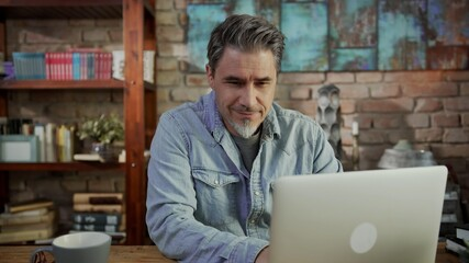 Mature man working from home, sitting at desk in home office using laptop, thinking, browsing internet, teleworking online.