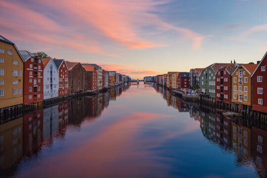 TRONDHEIM, NORWAY, july 2019: Sunrise view of colorful timber houses surrounding river Nidelva in the Brygge district of Trondheim, Norway